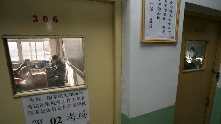 A group of people behind a closed door taking the national civil servant qualification exam in Beijing.