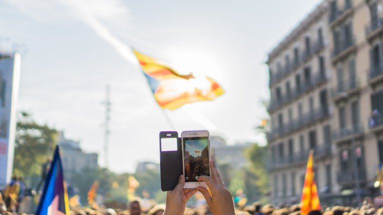 Mobile phone, held in hands, taking a photo of a street with crowds carrying flags.