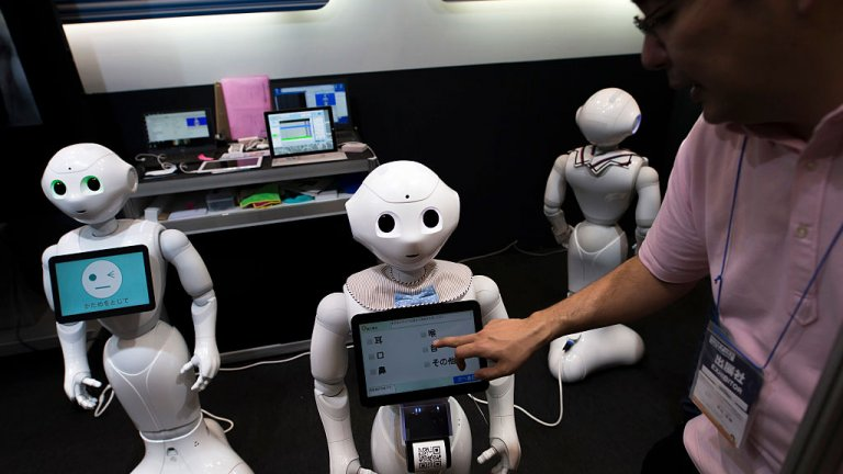 An attendant uses a tablet computer on a SoftBank Group Corp.'s Pepper humanoid robot at the Robodex Trade Show, Tokyo, Japan, 2017