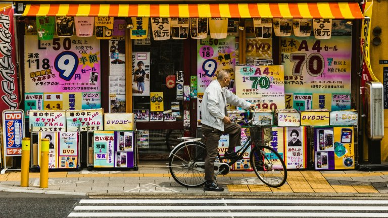 A man pauses on his bike in front of shop windows in Oshiage, Sumida, Japan