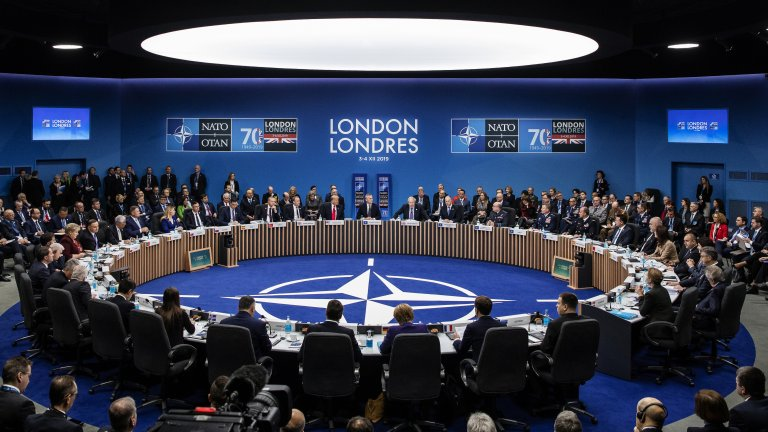 Members of NATO sit around table in conference