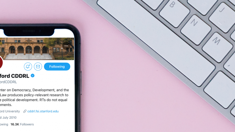 iPhone with CDDRL Twitter page on screen next to a keyboard on a pink background