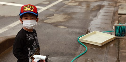 A young boy helps with clean-up efforts after the March 11 earthquake and tsunami. (Flickr/DJ Milky)