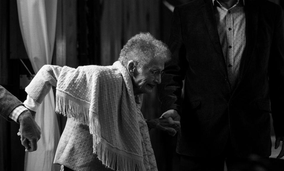 An elderly woman gets help walking