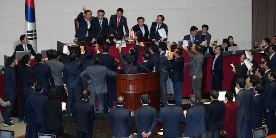 Chairman of the South Korean National Assembly Moon Hee-sang (second from the left of the chairman's seat) enacts a draft amendment to the election law amid vigorous resistance by members of the opposition –December 23, 2019.