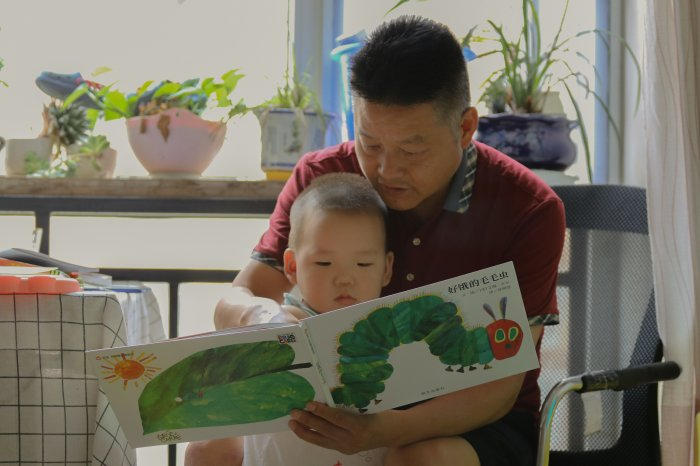 Father reads a picture book with his son at the dining table.