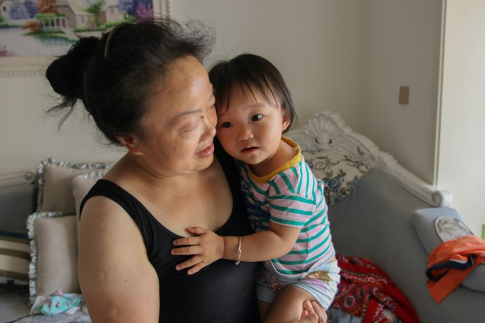 Child clings on to grandmother as the grandmother is interviewed.