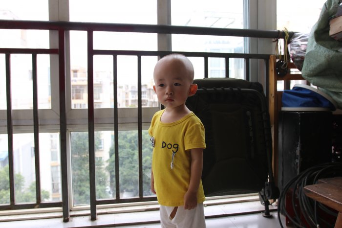 Child left alone in his apartment living room, staring at the camera.