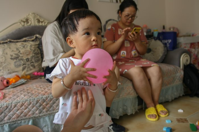 A toddler plays with a pink ball while their caregivers sit on the couch behind him looking at their phones.