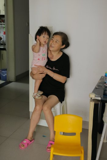 Grandmother holds onto her granddaughter while trying to comfort her.