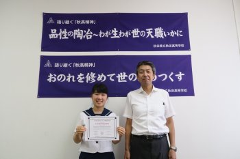 A student with a diploma with a teacher standing in front of a banner