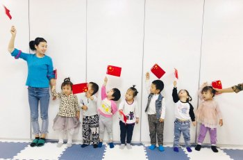 Toddlers stand in a line holding the Chinese flag with their parenting center manager.
