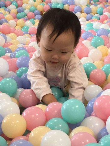 Baby plays with pastel colored balls in a ball pit.