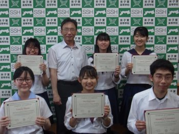 Five students holding diploma with a principle in front of a banner